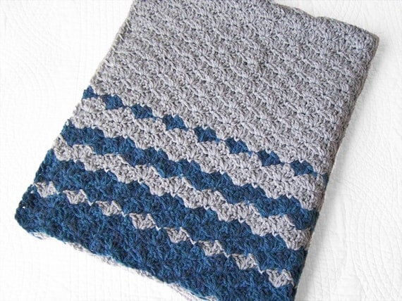 Crochet baby blanket in grey and stripes of variegated shades of blue