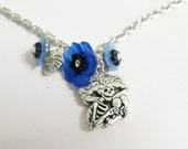 Maraca Playing Skeleton Necklace with Blue and Black Flowers
