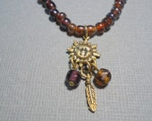 Brown Necklace Glass and Gold Sun Face Charm