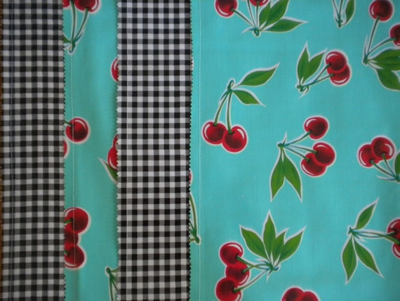 Reversible oilcloth placemats in a retro cherries pattern and black gingham