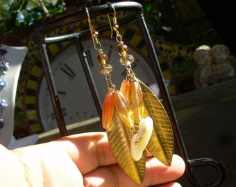 Here are a pair of OOAK Hand made Earrings Made with faceted crystal beads and faux Amber and shell and Leaf charm