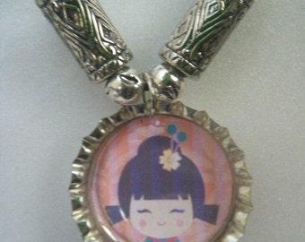 Japan-Kids Saving Kids - Bottlecap necklace featuring Kokeshi Face dolls artwork