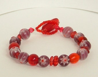 Bracelet with purple floral glass beads and red beads