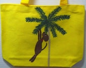 Hand-painted small yellow tote bag - whimsical dog design - hanging on a palm tree