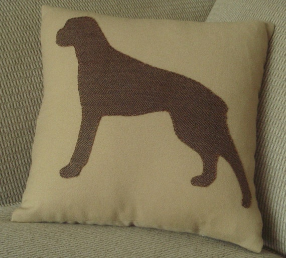 A Pillow with a  Boxer Silhouette Appliqued to a light golden brown top.