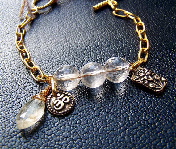 Gold Charm Bracelet with Lotus and Om Symbol Charms and Facted Crystal Clear Quartz Stones