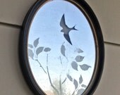 oval framed silver leaf mirror with bird