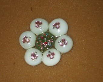glass flower shaped paper weight with gem-like embellishments