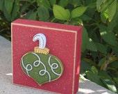 Green ornament on red block for Christmas, Noel, shelf, desk, office, mantle and home decor