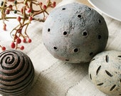 Group of three textured ceramic spheres in pale red, blue gray and yellow. 3