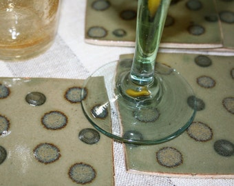 Set of four stoneware coasters with polka dots in mossy celadon. Khaki, green, rustic, earthy.