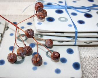 Set of four coasters in blue and white. Polka dots, matte, rustic, modern, hand made, hand painted.