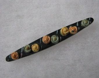Vintage black bar shaped pin w/ pastel flowers.  Needs repair