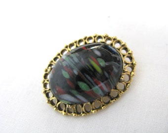 Oval black marbled pin brooch with gold tone filigree border