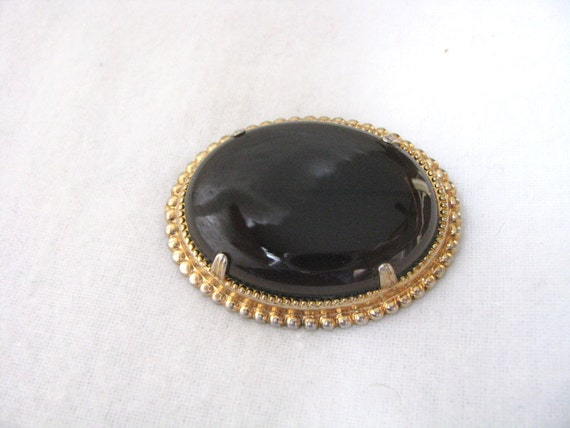 Beautiful black oval pin brooch with gold tone crimped setting