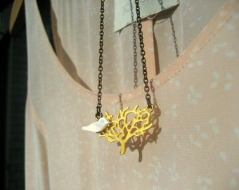 A white bird from the tree. A matt gold plated tree and a little bird in its branches, a romantic charm brass necklace.