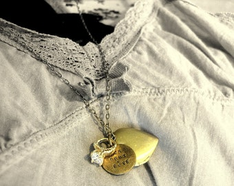 A heart locket, a romantic French message hand stamped in a brass tag and a small sparkling ring