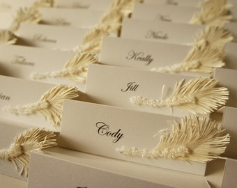 White wedding place cards with ivory feather & pearls decor