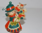 Little Plastic Christmas Ornament of German Girl Angel with a Bundle of Flowers