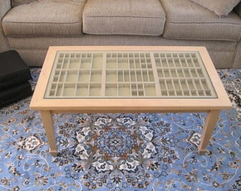 Wood coffee table with a printer's type tray in which you can display jewelry, seashells, and other collections of treasured items.