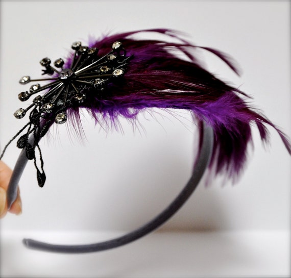 Plum purple headband-jeweled feathers. A chic classic with starburst spray of lavender and grey rhinestones.
