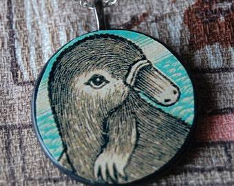 Cuddle Me Handmade Round Wood Pendant Necklace with Vintage Cute Platypus Illustration.