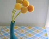 Peacock teal vase with mustard craspedia flowers.  Mod curved vase.  Billy balls.  Pom poms.  Floral arrangement.  Last One.