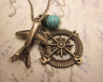 Travel the World. a charm necklace with airplane, compass and turquoise stone accent