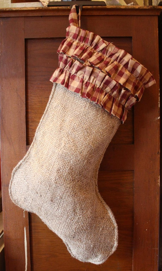 This rustic Christmas stocking features a flannel like cuff with intricate stitch-work on the body. Santa has a overly exaggerated beard which just makes him look all the more holly jolly, not to mention His bag is full of presents for the good boys and girls!