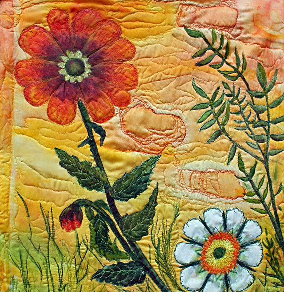 A fiber art wall hanging, an art quilt with modern stylized flowers in tangerine,yellow, green applique