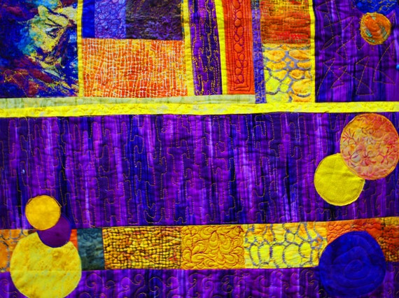 An art quilt for sale.Fiber art wall quilt in a geometric abstract style.Striking purple and gold colors.