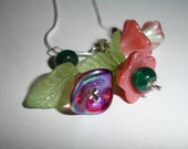 Sterling silver crosses in the center of beautiful, colorful, and vibrant  flowers on a sterling silver rope style chain
