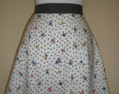 Vintage inspired half apron with colourful floral print and polka dot strap and pocket with button