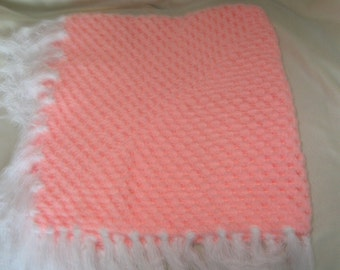 a crocheted pink shawl/blanket