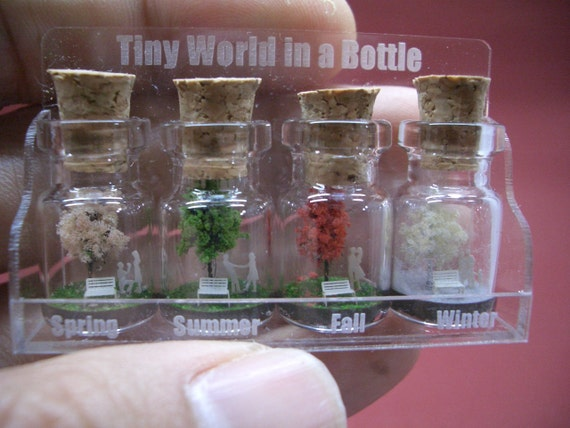 Tiny trees with a couple & family in four seasons in a tiny bottle in a small cute case