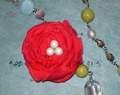 blue, green, and white beadd necklace, wit a red rosette
