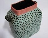A handmade polka dot ceramic vase/pen holder