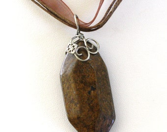 Single large 40 mm faceted stone of Bronzite wire wrapped on brown ribbon necklace
