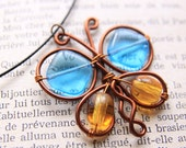 colorful butterfly pendant made with copper wire, blue and yellow glass beads