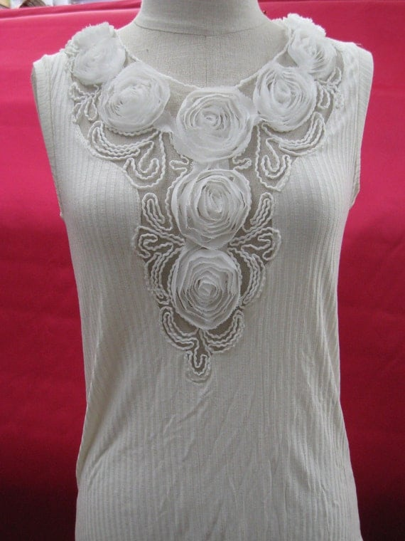 Cream color tank top with floral decoration in the front plus made in USA