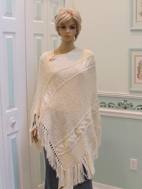 """Creme/ivory,  poncho,for a med. to large sized woman, hand knitted in a cable pattern, with 5"""" fringe"""