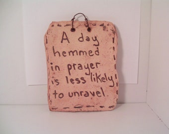 "Clay sign, ""A day hemmed in prayer is less likely to unravel."""
