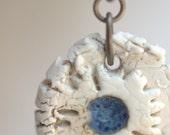 Rustic blue and cream porcelain floral pendant.