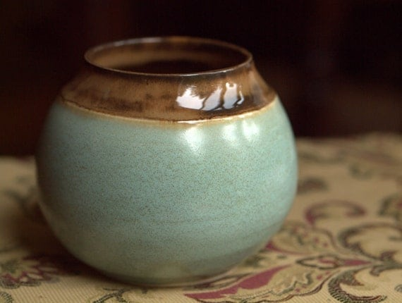 Small, round, wide mouthed vase in turquoise and caramel brown.