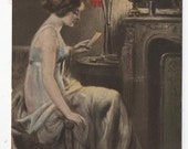 1917 colour illustrated postcard showing a fashionable young woman in evening dress reading a letter