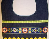 Denim bib with green and yellow trims and ribbons