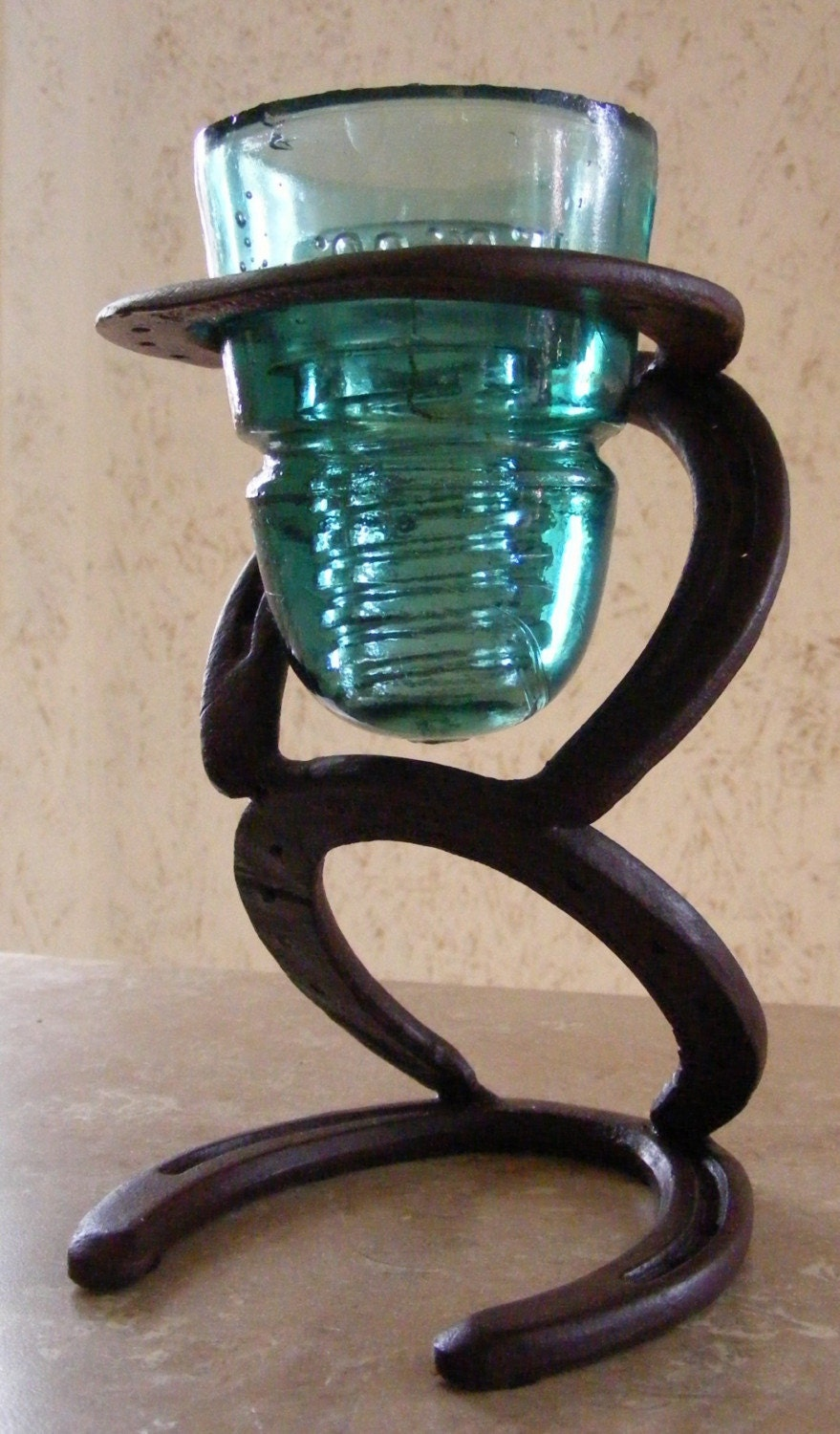 horseshoe and glass insulator candle holder
