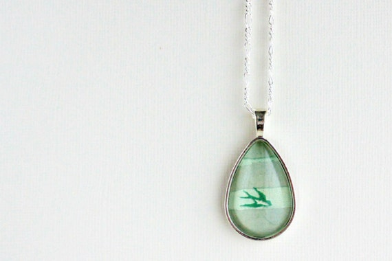 Flying bird necklace  Sheet music illustration in mint green and gray under glass.  Silver teardrop pendant.