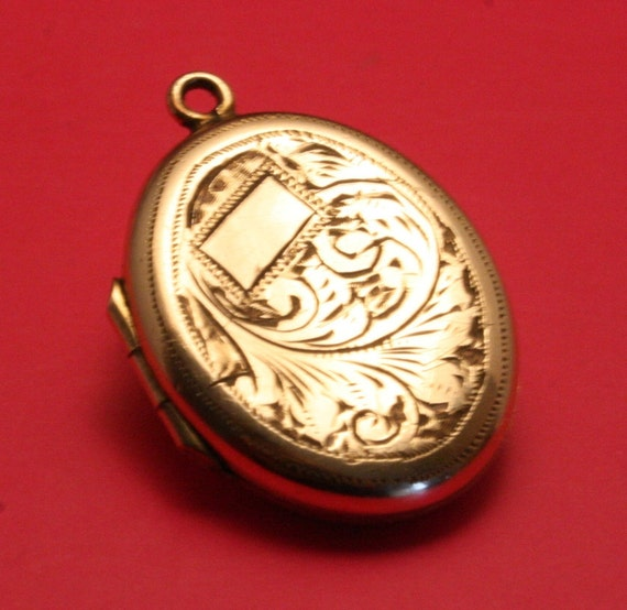 Vintage rolled gold  locket with ornate design and cartouche. Oval shape
