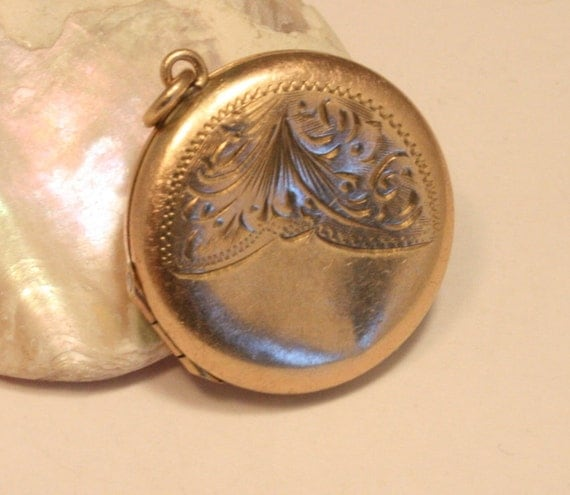 Vintage gold back and front locket. Round with ornate scrollwork
